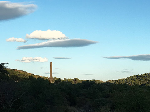 Factory chimney in La Caunette, with silver clouds. Photo by Giles Mitchell.